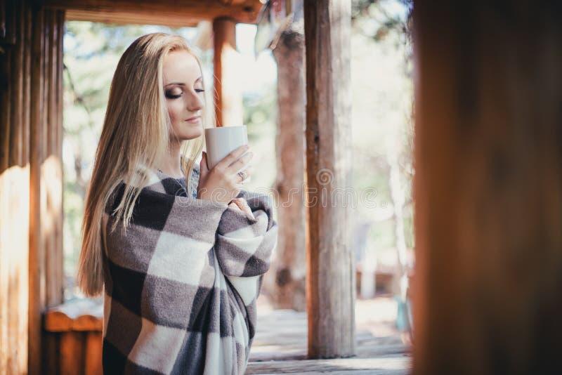 年轻美丽的妇女饮用的可可粉在一个木coutry房子里 免版税库存图片