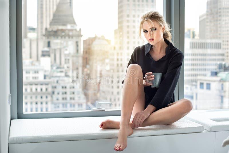 美丽的妇女饮用的咖啡在早晨在豪华城市顶楼房屋 免版税图库摄影