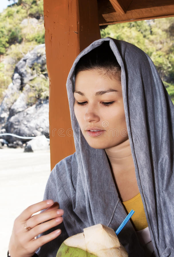 美丽的妇女饮用的椰子汁 免版税库存照片