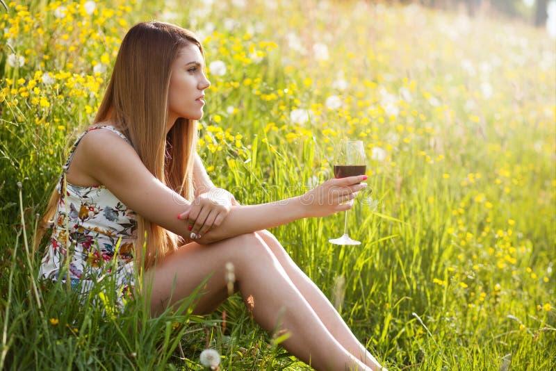 年轻美丽的妇女饮用的酒户外 免版税库存图片