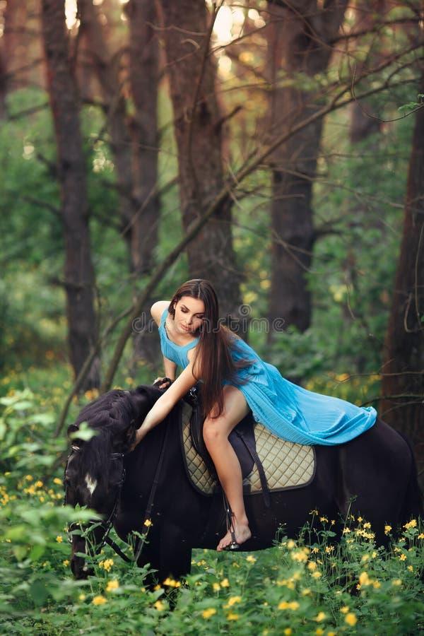 美丽的妇女骑乘马在森林里 图库摄影