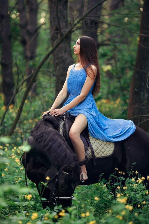 美丽的妇女骑乘马在森林里 免版税图库摄影