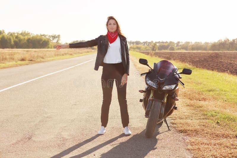 美丽的妇女骑自行车的人全长射击有自行车的问题在路,搭车并且请求司机帮忙,穿戴在时髦 库存照片