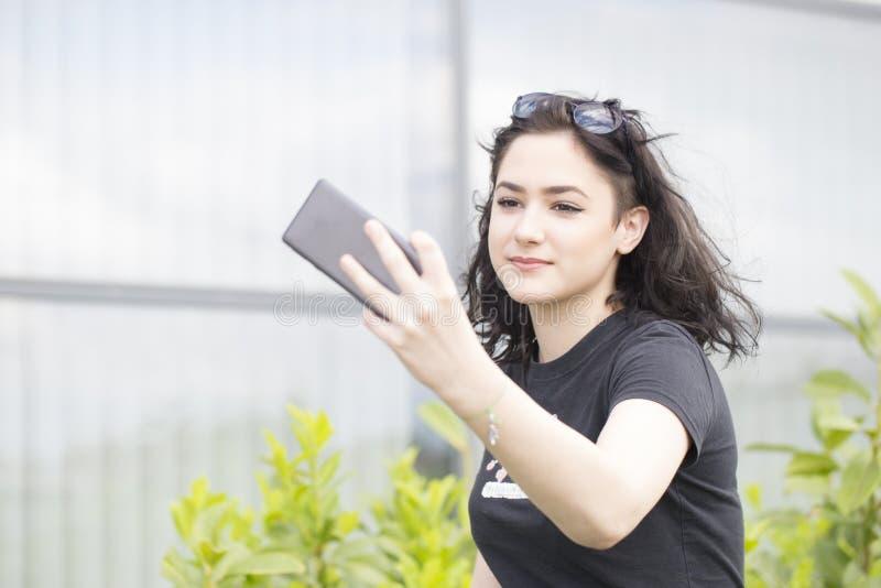 年轻美丽的妇女,行家,拿着手机手中和 免版税库存照片