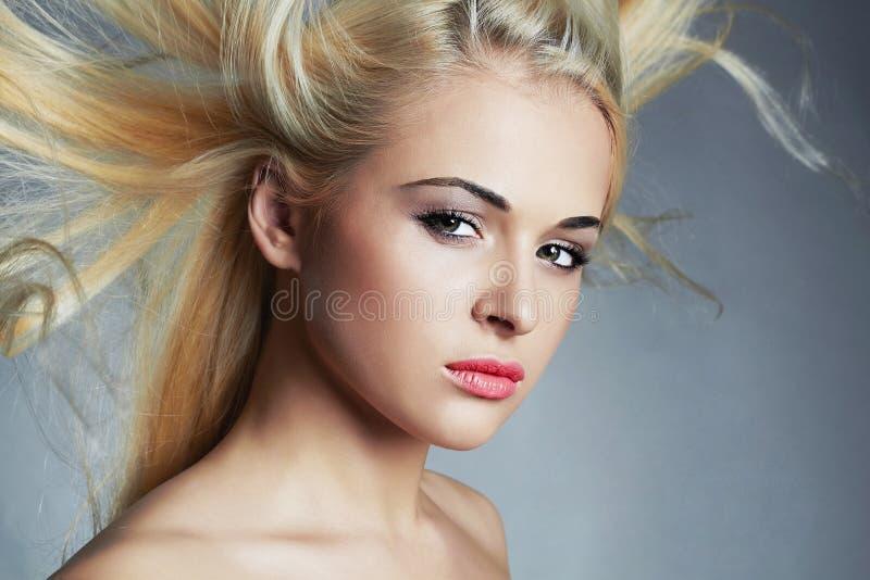 美丽的妇女年轻人 性感白肤金发的女孩 擦亮沙龙的秀丽nailfile钉子 haircare Flyi ng头发 库存照片