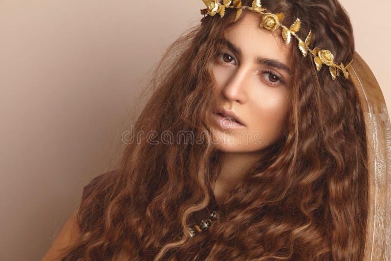 美丽的妇女 卷曲长的头发 礼服方式金黄设计 健康波浪发型 赞誉 秋天花圈,金花卉冠 免版税库存照片