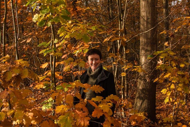 美丽的妇女60在一个美丽的秋天森林里 图库摄影