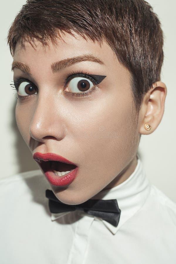 年轻美丽的妇女以短发样式和经典穿戴与蝶形领结 免版税图库摄影