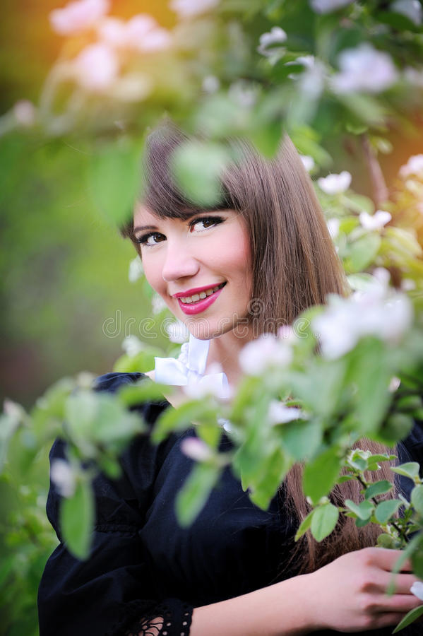 年轻美丽的妇女画象在春天庭院里 库存图片