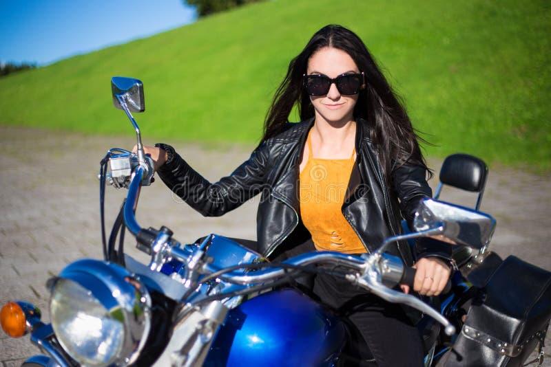 美丽的妇女画象坐减速火箭的摩托车 免版税库存照片