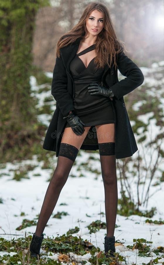 年轻美丽的妇女画象室外在冬天风景 有长的腿的肉欲的浅黑肤色的男人在黑长袜摆在时兴 库存照片