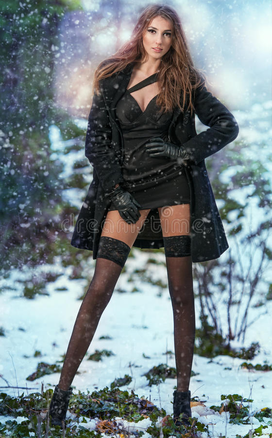 年轻美丽的妇女画象室外在冬天风景 有长的腿的肉欲的浅黑肤色的男人在黑长袜摆在时兴 库存图片