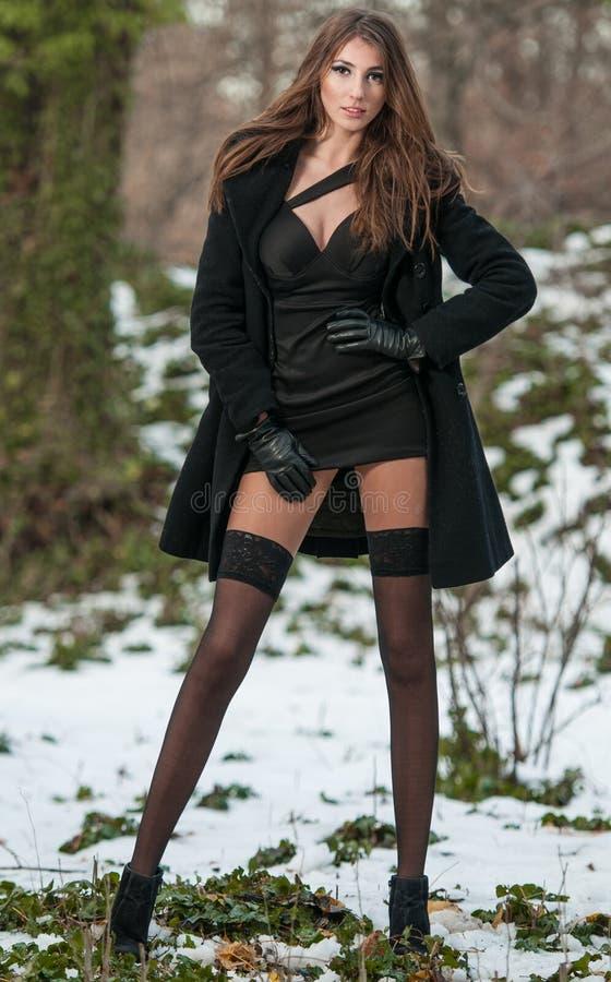 年轻美丽的妇女画象室外在冬天风景 有长的腿的肉欲的浅黑肤色的男人在黑长袜摆在时兴 免版税库存图片