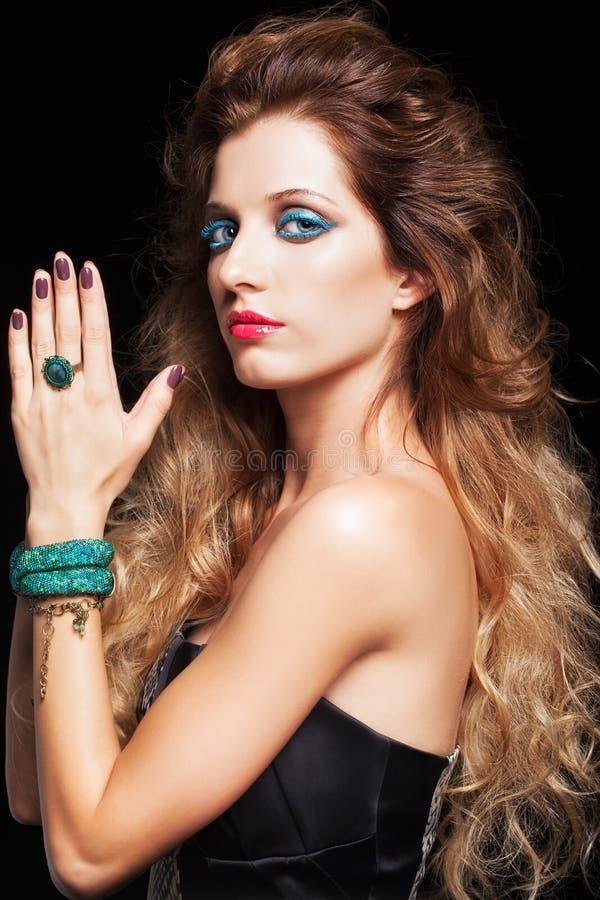 年轻美丽的妇女画象有卷曲粗野的发型的 免版税图库摄影