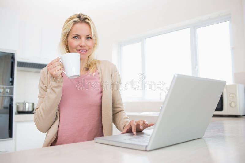 美丽的妇女画象有咖啡杯的使用膝上型计算机在厨房里 图库摄影