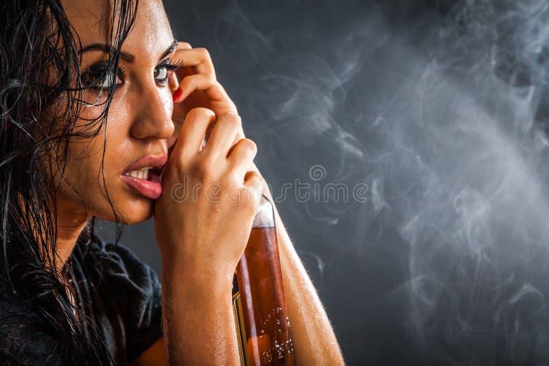 美丽的妇女画象有瓶的酒精饮料 免版税库存图片