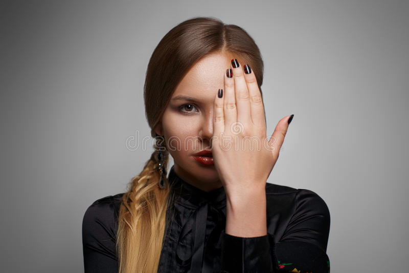 美丽的妇女画象用在面孔前面的手 库存图片