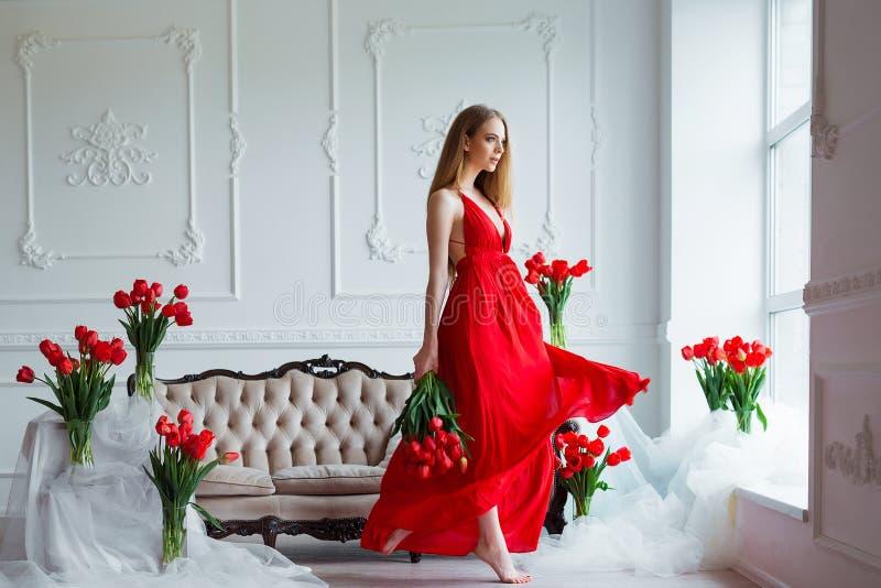 年轻美丽的妇女画象红色礼服的有在豪华内部的郁金香的 图库摄影