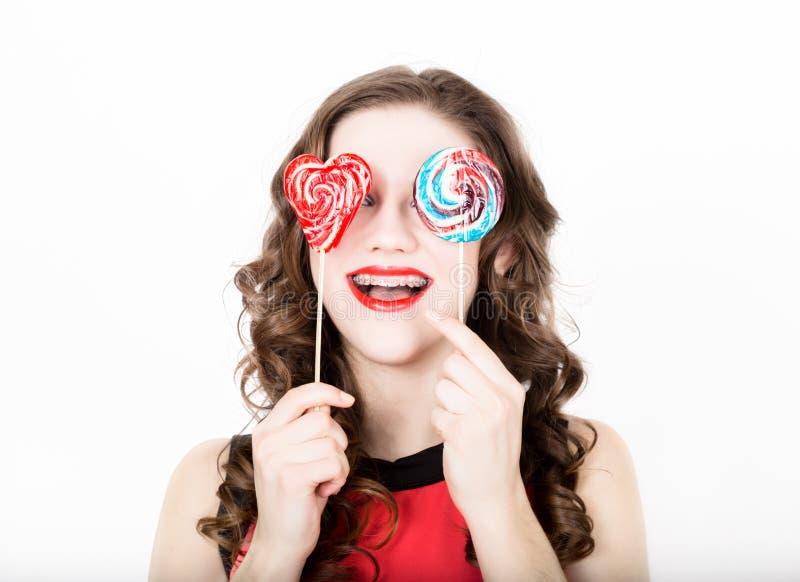 年轻美丽的妇女画象戴牙齿括号和糖果眼镜的 库存照片