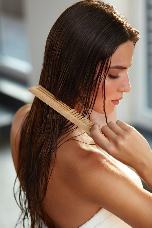 美丽的妇女Hairbrushing她长的湿头发 护发 免版税库存照片