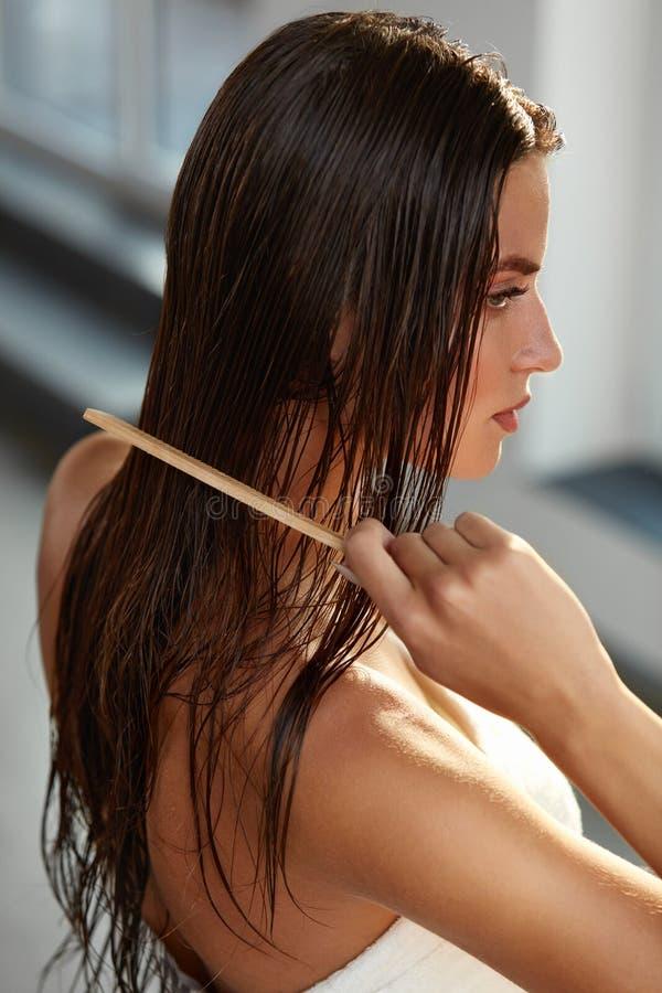 美丽的妇女Hairbrushing她长的湿头发 护发 库存图片