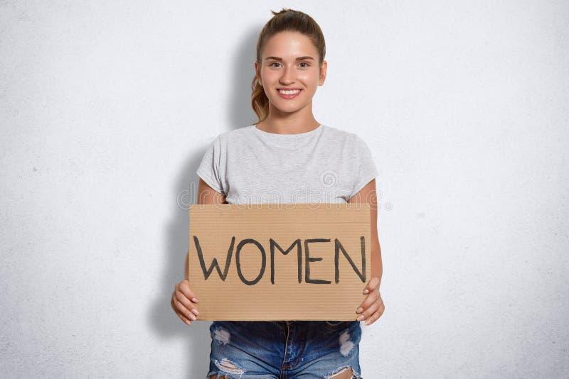 美丽的妇女Portait有柔和的微笑,穿戴随便,有标志妇女的举行板材,是女权,姿势反对白色ba 免版税库存照片