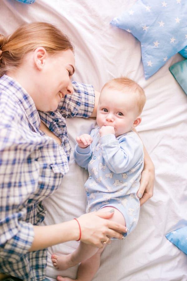 美丽的妈妈画象使用与她的婴孩的衬衣和蓝色牛仔裤的 库存图片