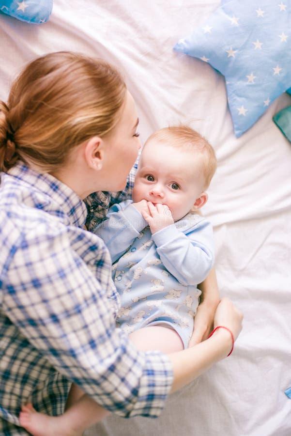 美丽的妈妈画象使用与她的婴孩的衬衣和蓝色牛仔裤的 免版税库存图片
