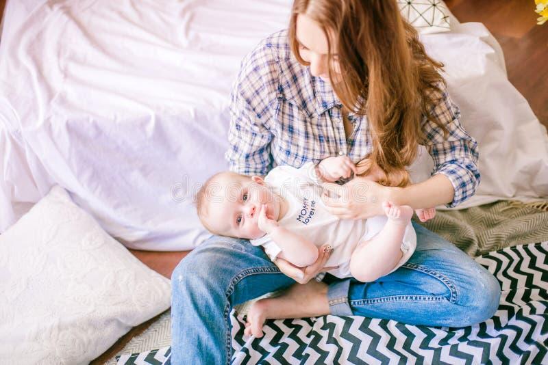 美丽的妈妈画象使用与她的婴孩的衬衣和蓝色牛仔裤的 库存照片