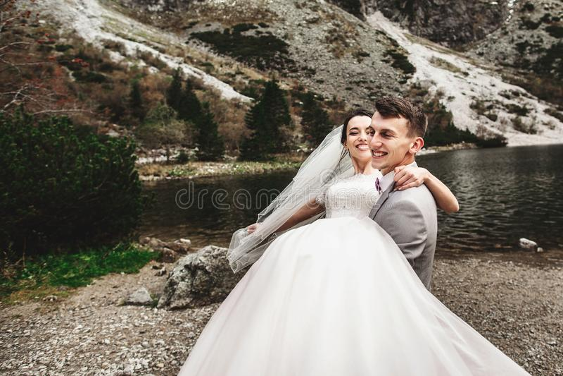 美丽的婚姻的photosession 新郎盘旋他的年轻新娘,湖Morskie Oko的岸的 ?? 免版税图库摄影