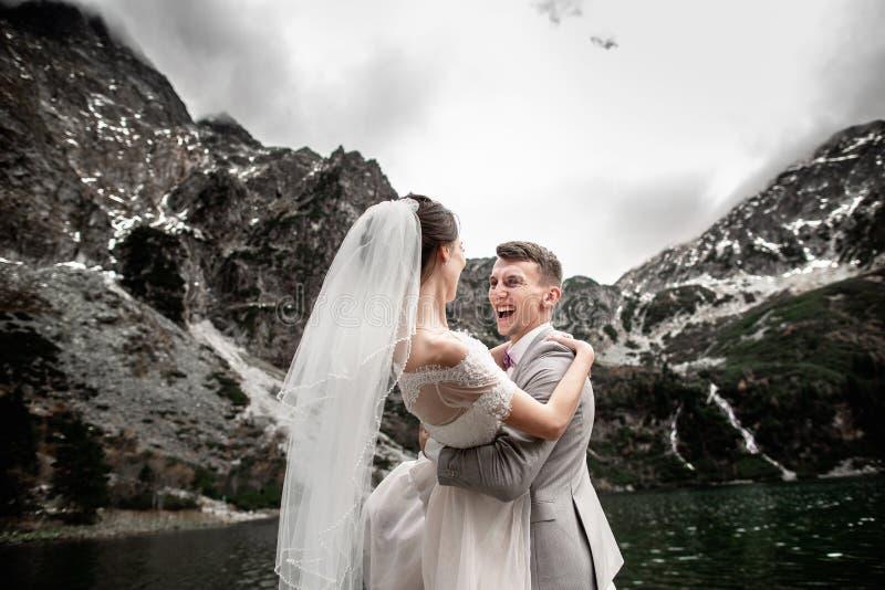 美丽的婚姻的photosession 新郎盘旋他的年轻新娘,湖Morskie Oko的岸的 ?? 免版税库存照片