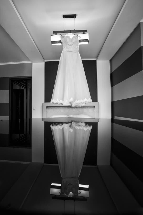 美丽的婚礼礼服垂悬在屋子里的,新娘辅助部件, 免版税库存图片