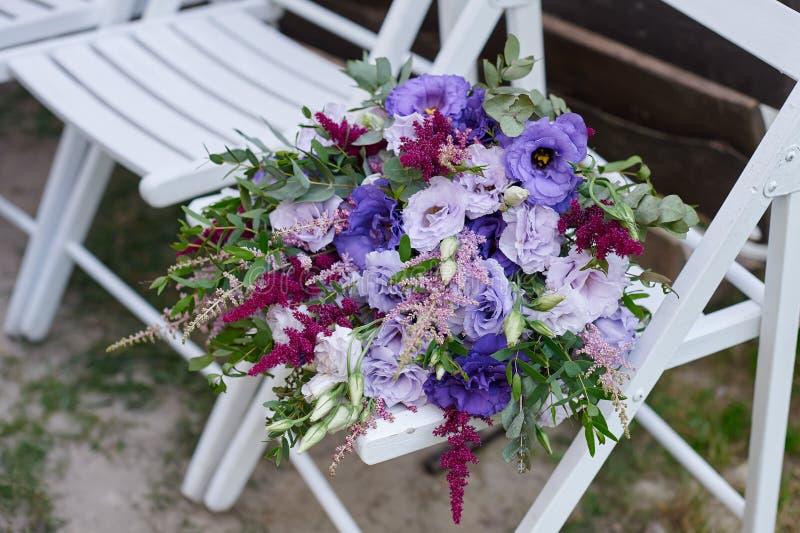 美丽的婚礼花束一把椅子的新娘仪式的 免版税库存照片