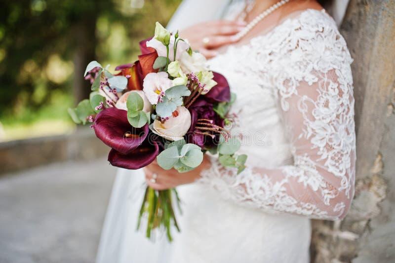 美丽的婚礼花束的特写镜头照片在新娘` s手上 免版税库存照片