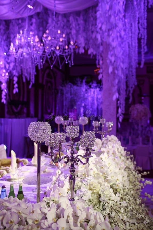美丽的婚姻的餐馆内部桌装饰 花 白色兰花和佐仓花瓶的 蜡烛 免版税库存照片