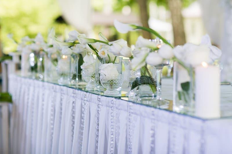美丽的婚姻的餐馆内部桌装饰 花 白色水芋百合和郁金香在花瓶 蜡烛 库存照片