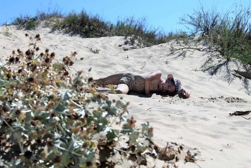 美丽的婴孩疲乏说谎在沙子和棕褐色和休息 库存图片