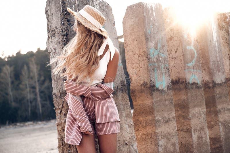 美丽的嫩年轻女人在草帽在阳光下摆在 乡下风景,在背景的森林自然 免版税库存照片