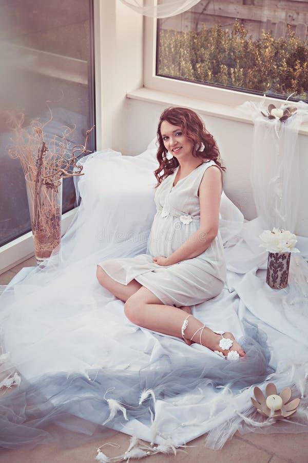 美丽的孕妇在家 库存图片