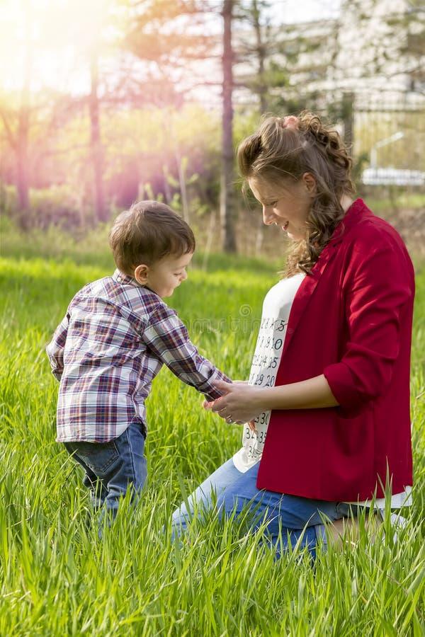美丽的孕妇室外与她的小男孩 库存照片