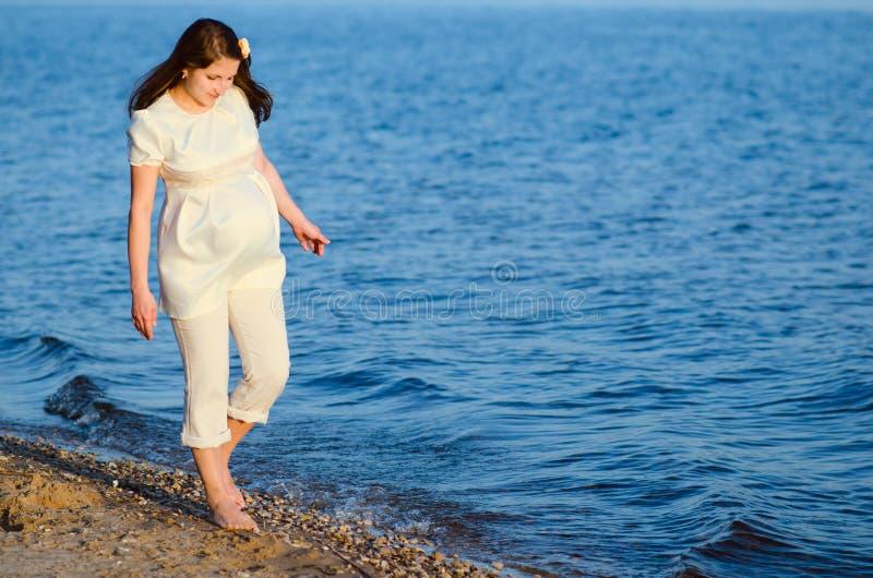 美丽的孕妇沿岸走 免版税库存照片