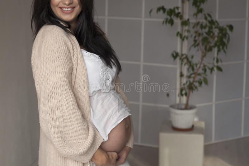 美丽的孕妇画象在交付前的在白色 库存照片