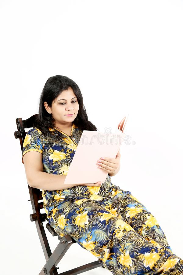 美丽的孕妇读与的婴孩杂志坐椅子 免版税库存图片
