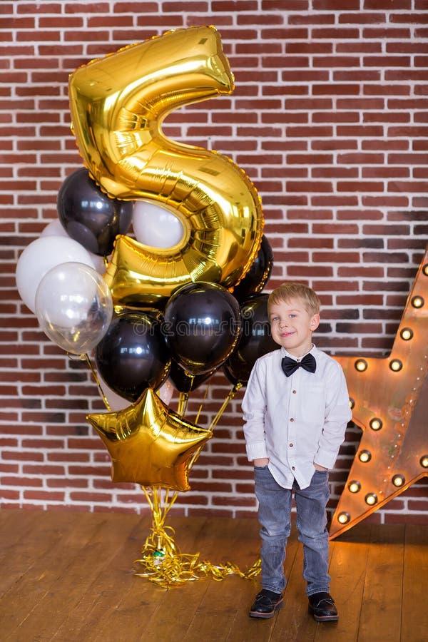 美丽的孩子,庆祝生日和吹在自创被烘烤的蛋糕的小男孩蜡烛,室内 生日聚会为 库存照片