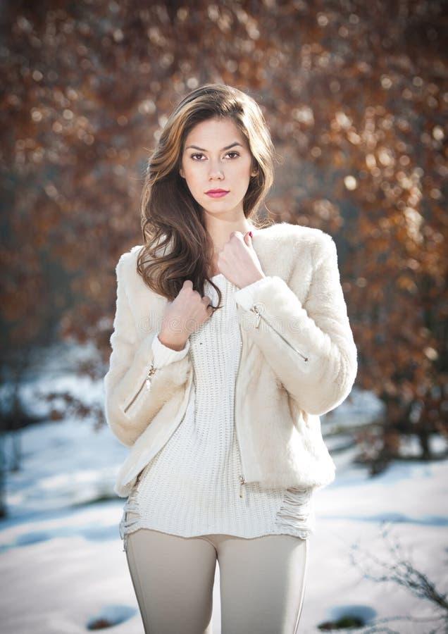 年轻美丽的室外妇女佩带的白色的衣裳画象。有长头发摆在的美丽的深色的女孩室外在冬天 免版税库存图片