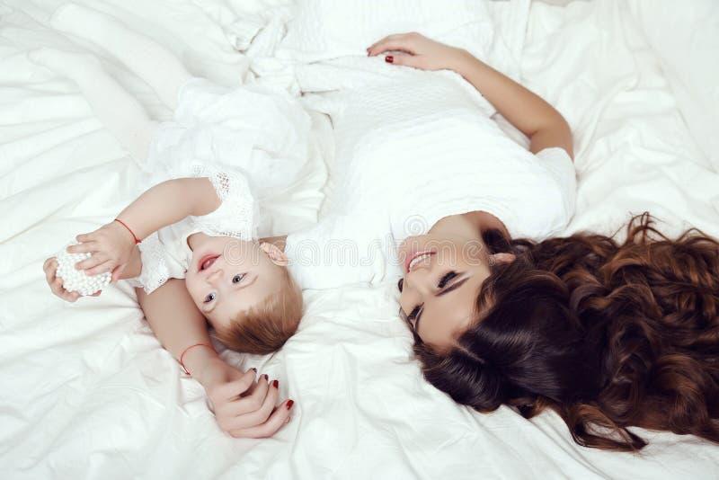 美丽的家庭照片 有她的小逗人喜爱的女婴的华美的母亲 免版税库存照片