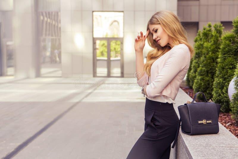 美丽的富有的偶然白肤金发的时髦的时装业妇女与 免版税库存图片