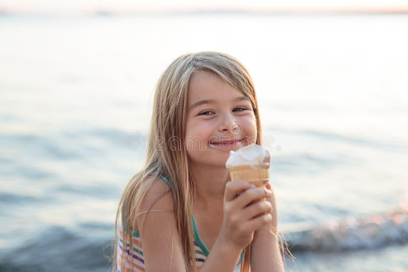 美丽的小女孩在夏天吃冰淇凌 免版税库存照片