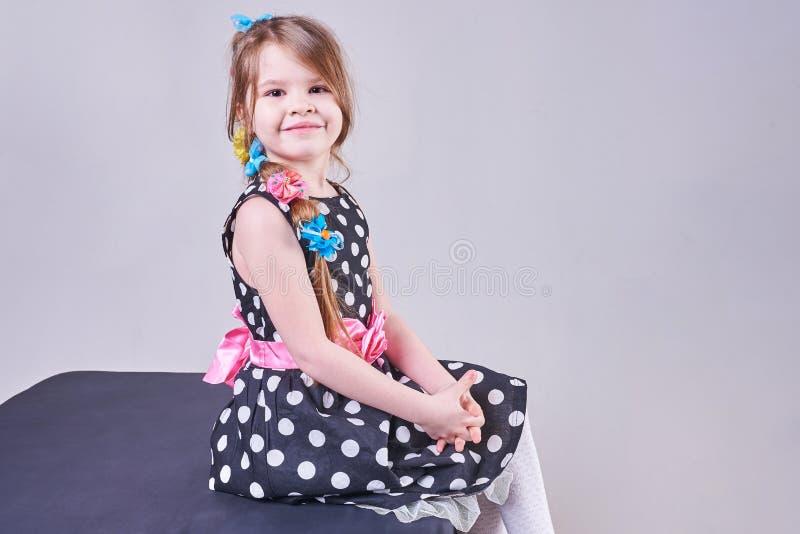 美丽的小女孩坐一个黑立方体 库存图片