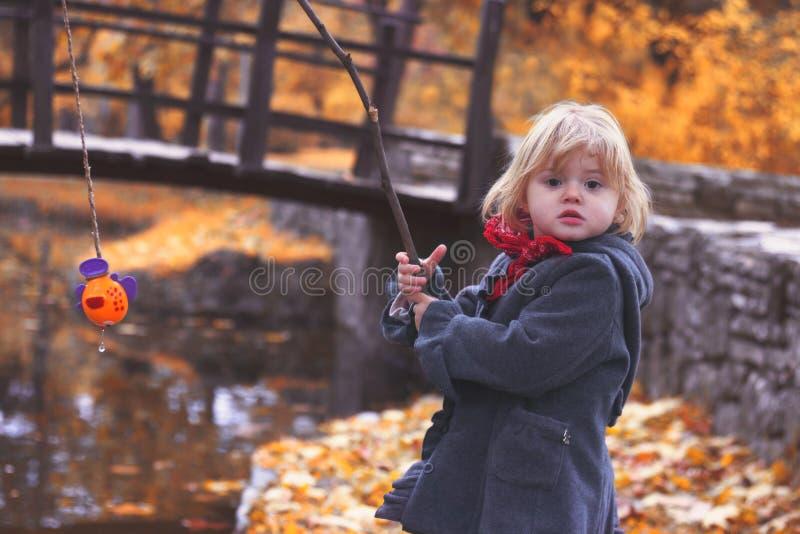 美丽的小女孩演奏与分支的渔和鱼戏弄 免版税库存照片